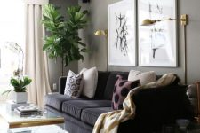 a lovely greige living room with a black sofa, a mini gallery wall, gold sconces, acrylic side tables and a coffee table plus statement plants