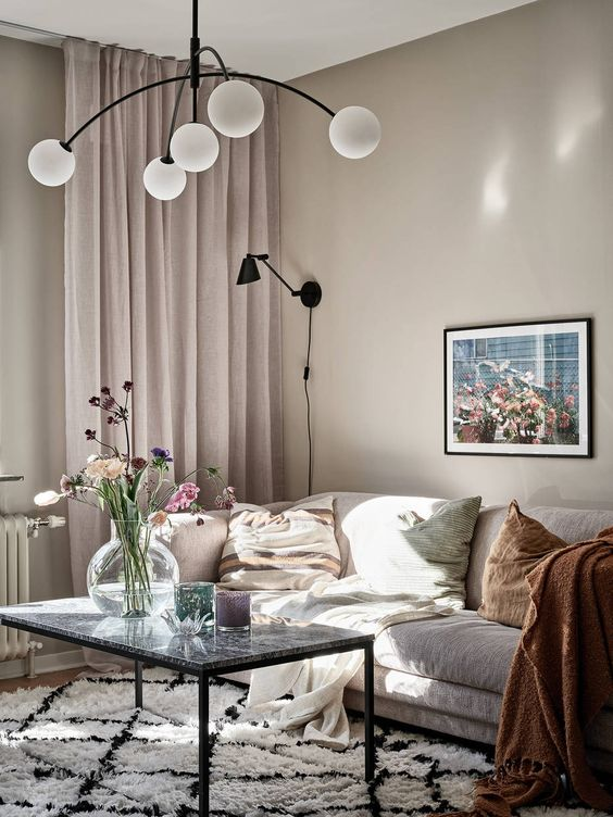 a lovely greige living room with a neutral sofa, a table with a stone tabletop, blush curtains, muted color pillows and a pretty chandelier