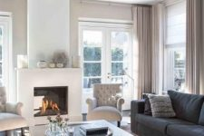 a lovely greige living room with greige textiles, a fireplace, graphite grey sofas, a wooden coffee table and elegant creamy chairs