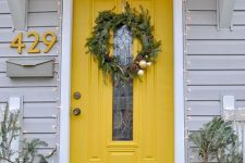 a lovely marigold front door with a glass pane, with a yellow house number on the wall styled for window is amazing