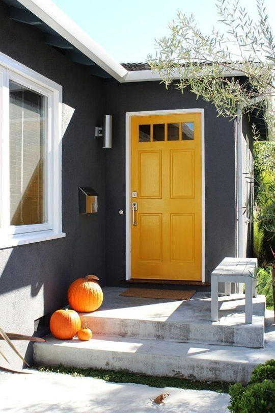 a marigold door with glass panes makes a bold statement with graphite grey walls around and orange pumpkins on the steps is a cool modern solution