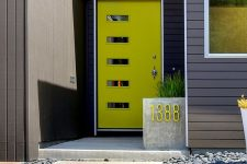 a mid-century modenr neon green front door with glass pants and a concrete planter with a neon green house number for a modern home