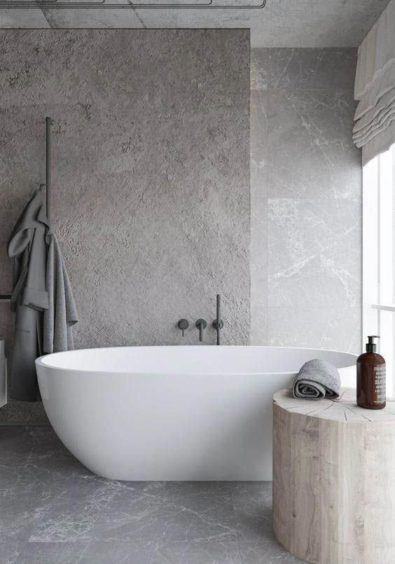 a minimalist and refined greige bathroom fully clad with stone, with a large tree stump side table and an oval tub is chic