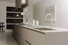 a minimalist greige kitchen with a sleek oversized kitchen island, a hood and hanging lamps plus built-in niches for tableware