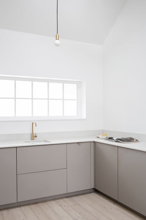 a minimalist greige kitchen with sleek cabinets, white stone countertops, brass touches and white walls is amazing