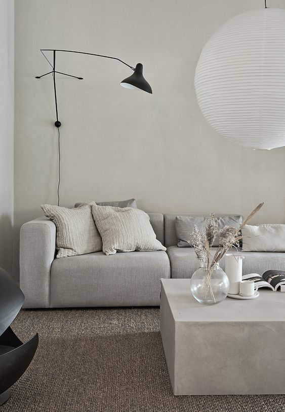 a minimalist greige living room with a grey sofa, a greige stone coffee table, a black sconce and a pendant lamp is amazing