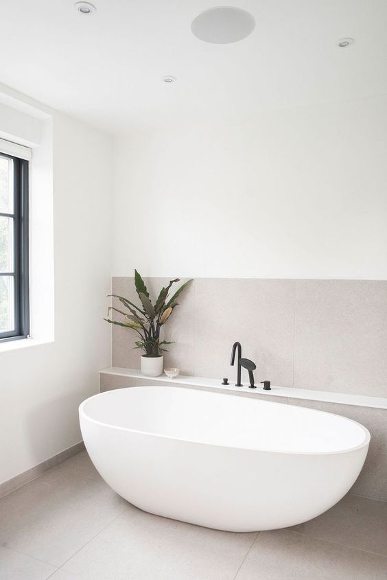 a minimalist serene bathroom clad with greige tiles, with an oval tub, black fixtures and a potted plant plus a window to enjoy natural light