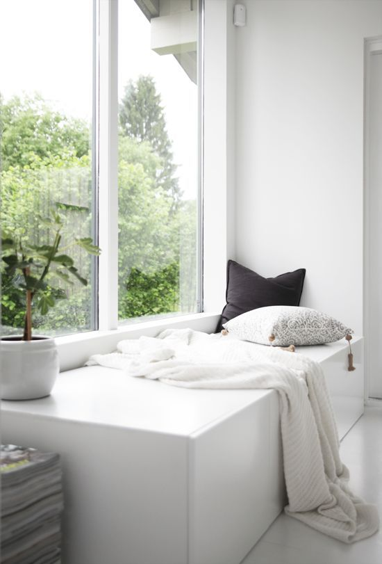 a minimalist space with a double height window and a storage daybed built in, with pillows and a blanket is a cool and stylish idea