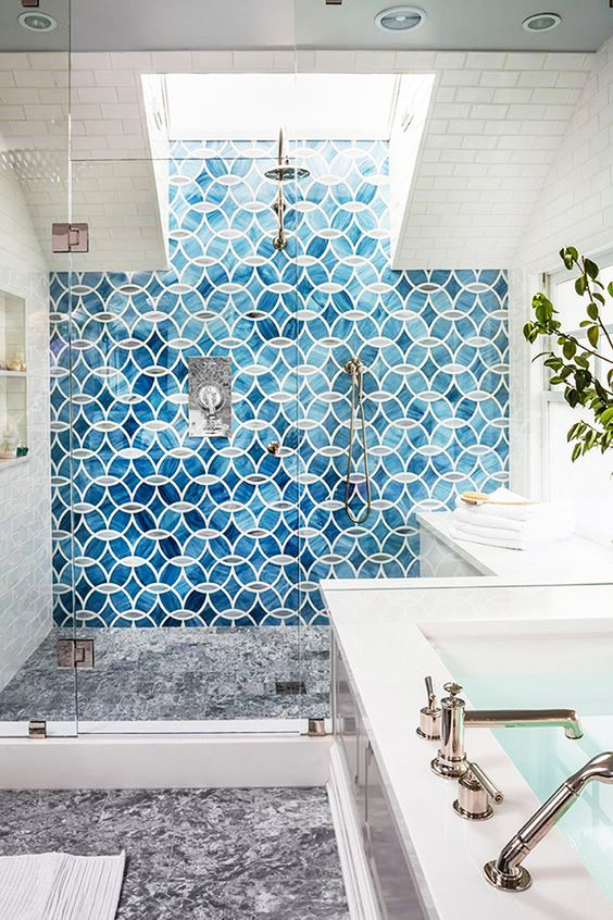 a modern and elegant bathroom with blue tiles in the shower and a skylight brightens up the shower space and makes it more inviting