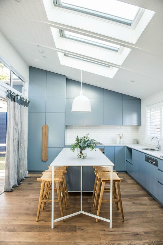 a modern blue kitchen and dining space are lit not only with windows but also with the help of skylights