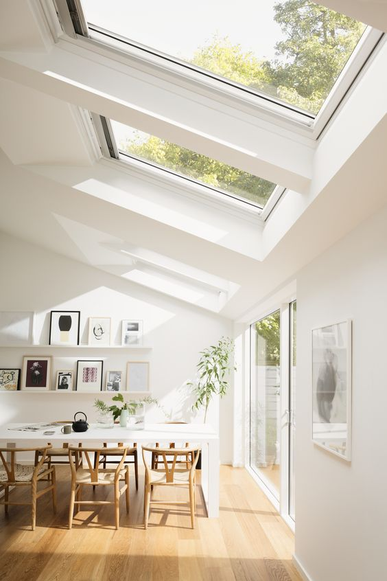 a modern dining space with a white table and wooden chairs, skylights and a glazed wall to maximize the views