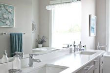 a modern farmhouse greige bathroom with a matching vanity with a white stone countertop, white appliances and neutral fixtures plus wall lamps