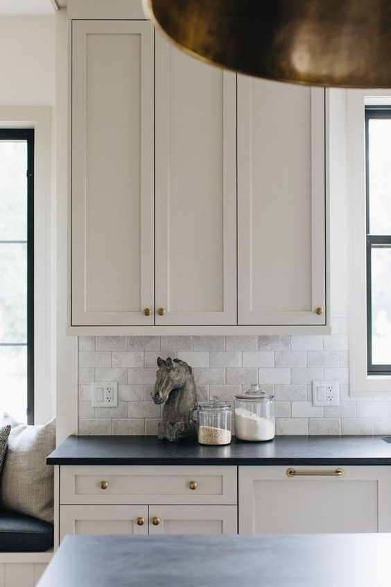 a modern farmhouse mushroom kitchen with shaker cabinets, black stone countertops, brass handles and knobs, a neutral tile backsplash