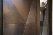 a modern geometric dark metal door with a 3D part and with a window by its side is a cool idea for a modern home