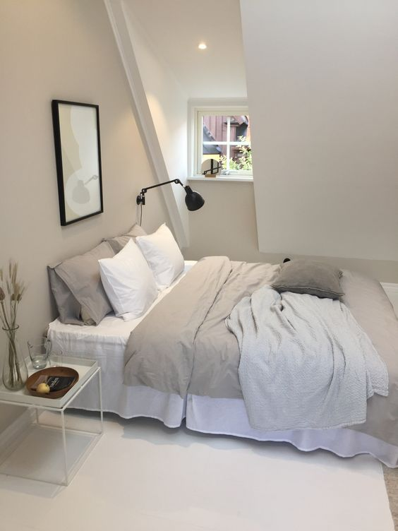 a modern greige attic bedroom with a bed, a nightstand and a black sconce, neutral and greige bedding, a small artwork is a cozy little sleeping space