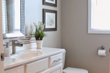 a modern greige bathroom with white furniture and appliances, a mirror in a mirrored frame, sconces and a mini gallery wall is cool