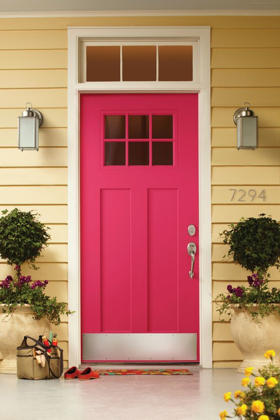 a modern pink front door with glass panes, potted blooms around for a lovely and bright entrance to the house
