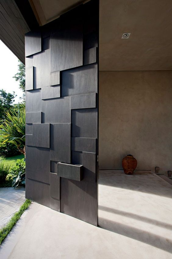 a modern sculptural and geometric oversized black front door is a cool idea for any modern or contemporary home