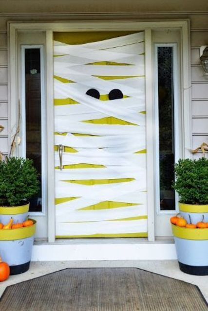 a neon neon yellow door styled as a mummy, with pumpkins in planters around is a lovely and playful solution for Halloween