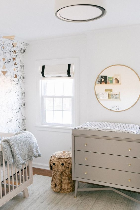 a neutral and pretty nursery with a wallpaper accent wall, greige furniture, a round mirror, ledges with books and an elephant basket for storage