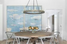 a neutral farmhouse dining room with light-stained wooden beams, a greige round table and chairs, a cool chandelier and a blue artwork on the wall