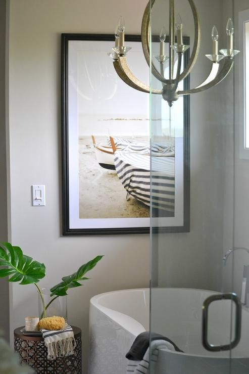 a neutral master bathroom featuring greige walls, a chandelier above a freestanding tub designed and a lovely coastal artwork