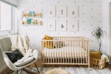 a neutral nursery with a wallpaper accent wall, a light stained crib, jute poufs, a white rocker, a grid gallery wall and open shelves