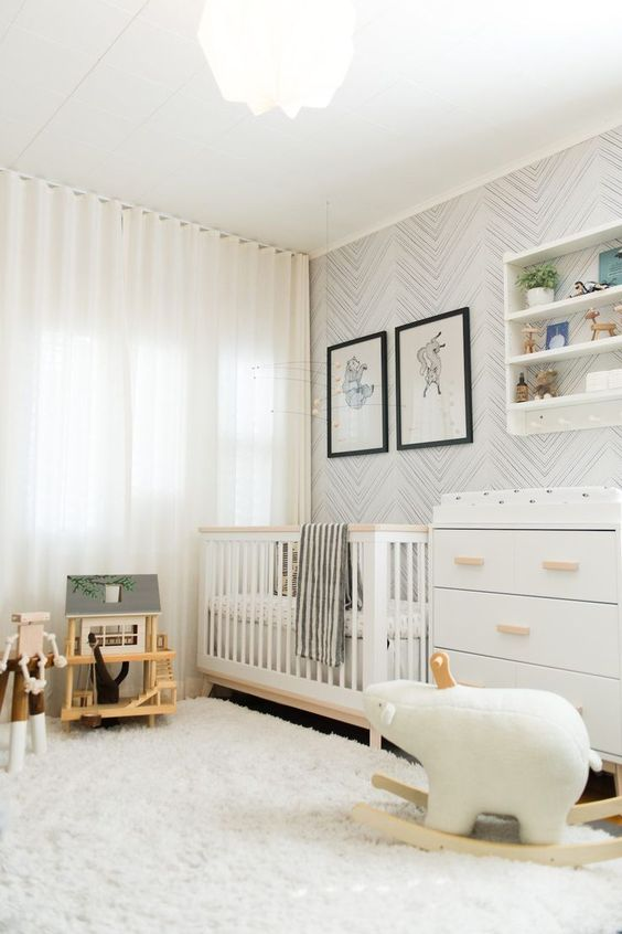 a neutral nursery with white and stained furniture, an open shelving unit, a wallpaper accent wall and some lovely and simple toys