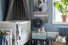 a pastel nursery in Scandi style with blue walls, a white crib, a dreamy artwork, some suitcases and a basket for storage and cool toys