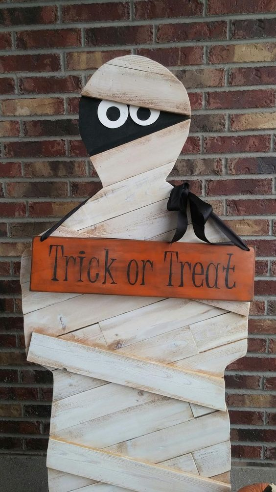 a plywood mummy is a very lon-lasting decoration that you can easily make, add a sign and a crate with sweets and candies
