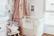 a pretty Scandi nursery with white furniture, a pink canopy with lights, some neutral and pastel layered rugs, a wallpaper accent wall and some artworks