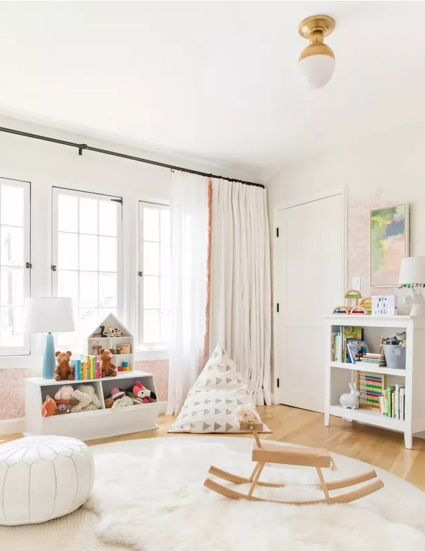 a pretty Scandi nursery with white furniture, white layered rugs, some touys, poufs and neutral curtains and pastel touches