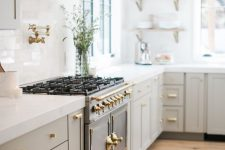 a pretty and refined greige kitchen with shaker cabinets, gold handles and white stone countertops, a white tile backsplash and open shelving
