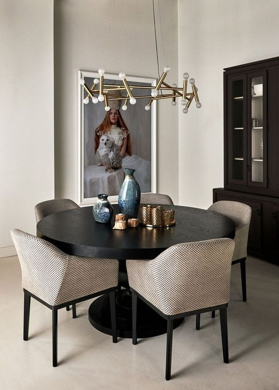 a pretty greige dining room with a dark stained storage unit, a black round table, greige chairs, a gilded chandelier and a large and bold artwork