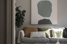 a pretty greige living room with a grey sofa, a low coffee table, muted color pillows, an abstract artwork and a statement plant