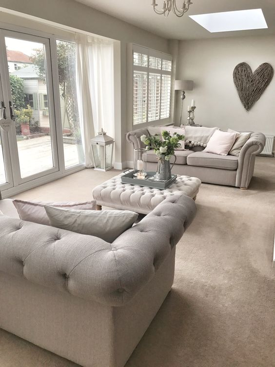 a pretty greige living room with matching tufted sofas, a tufted ottoman, a chandelier, a driftwood heart and some elegant floor and table lamps