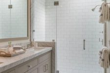 a pretty neutral bathroom clad with subway tiles, with a greige vanity with a white stone countertop and a skylight over the shower