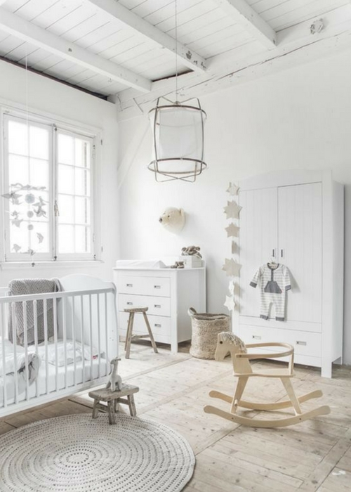 a pure white Scandinavian nursery with a dresser, a wardrobe, a crib, some stools and a pendant lamp plus pretty and cute decor