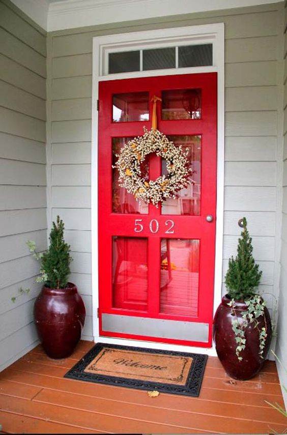 a red glass front door plus an additional red door inside and burgundy planters with greenery for a super bright entrance to the house