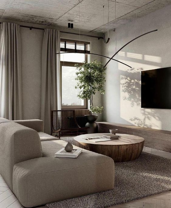 a refined contemporary greige living room with a neutral low sofa, a metal coffee table, pendant lamps and neutral curtains is chic