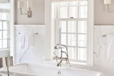 a refined greige bathroom with white marble tiles, a square tub, vintage fixtures and a beautiful chandelier plus a navy chair