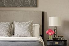 a refined greige bedroom with a greige bed, black elegant nightstands, an upholstered bench and an abstract artwork over the bed