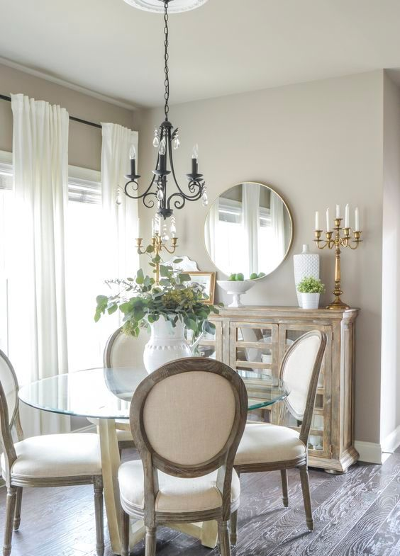 a refined greige dining nook with a reclaimed credenza, a glass round table, white chairs, a vintage chandelier and a chic candelabra