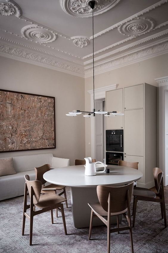 a refined greige dining room with a molded ceiling, a sleek round table, plywood chairs, a bold artwork, a storage unit with built in appliances