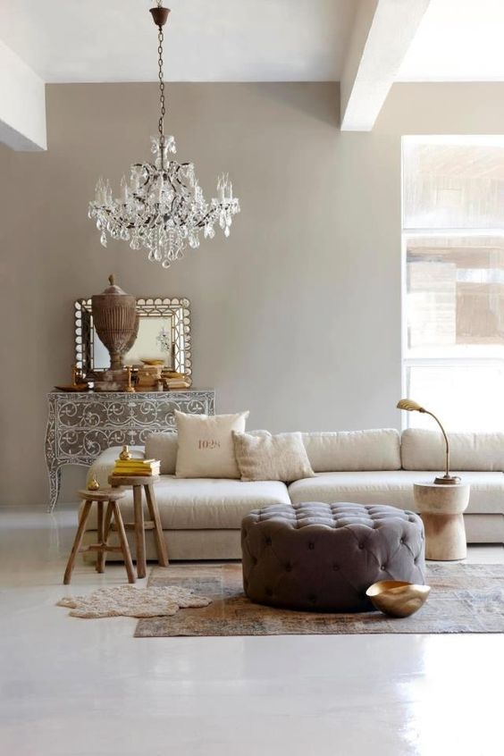 a refined greige living room with a neutral sectional, a taupe tufted pouf, side tables, a crystal chandelier and a beautiful ornated sideboard is wow