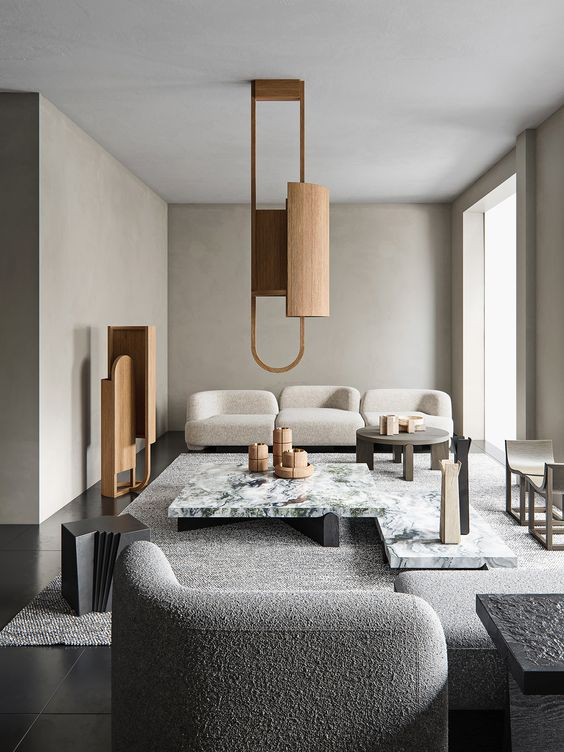 a refined greige living room with curved seating furniture, a white stone coffee table, a wooden pendant lamp and a matching decoration is chic