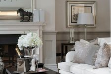 a refined neutral living room with greige paneling, a built-in fireplace, a white sofa, a black coffee table and an elegant gallery wall