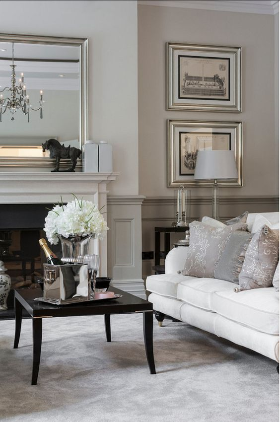 a refined neutral living room with greige paneling, a built in fireplace, a white sofa, a black coffee table and an elegant gallery wall