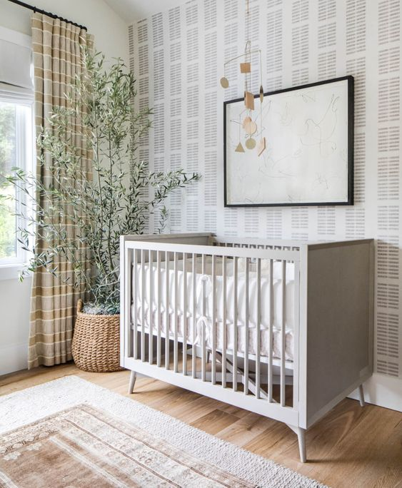 a relaxed Scandinavian nursery with printed wallpaper, a grey crib, an artwork, a mobile, a potted tree, layered rugs and striped curtains