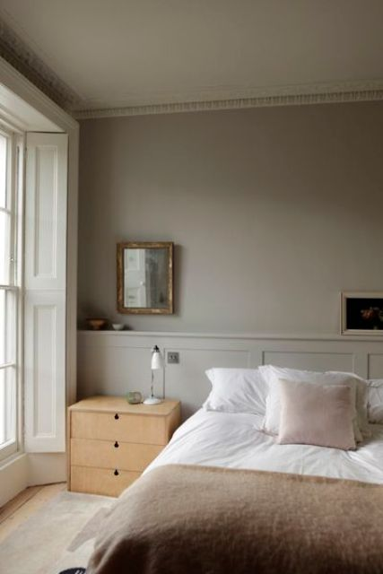 a relaxing greige bedroom with paneling, a bed with neutral bedding, light stained nightstands, artworks and mirrors plus a mirror with shutters